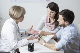stock photo of insemination  - Young marriage paying for expensive IVF process - JPG