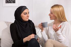 picture of muslim  - Pretty blond caucasian woman drinking tea with muslim - JPG