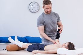 picture of schoolboys  - Schoolboy after wrist injury exercising with physiotherapist - JPG