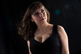 foto of curvy  - Portrait of curvy woman with flowing hair on black background - JPG