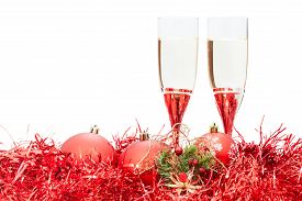 foto of christmas angel  - two glasses of sparkling wine and angel figure at red Christmas balls and tinsel isolated on white background - JPG