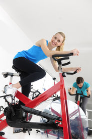 stock photo of exercise bike  - happy women on bike at the gym - JPG