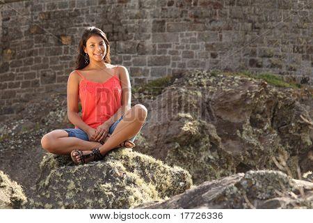 Pretty girl sitting on rock
