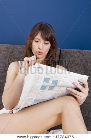 Beautiful young woman lying on the bed and seek for a job on the newspaper