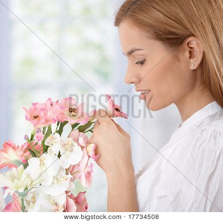 Beautiful young woman smelling flowers.?