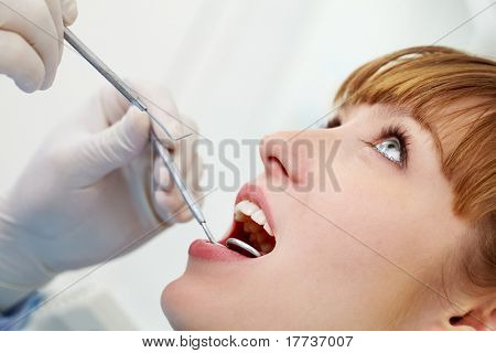 Photo of female open mouth during oral inspection with mirror and hook