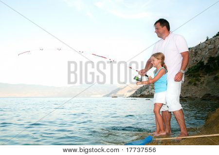 Fishing - little girl fishing with father at the beach