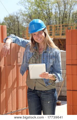 Smiling architect on building site with electronic tablet