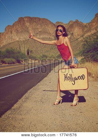 Jovem pegando uma carona na estrada deserta solitária
