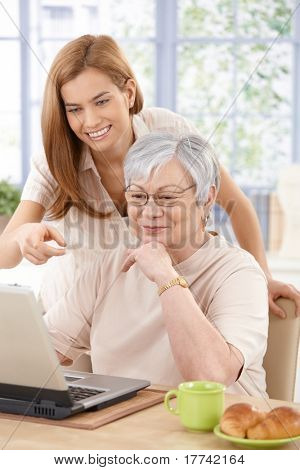 Mother and adult daughter using laptop, having fun, smiling.?