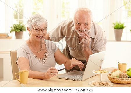 Portrait of happy old couple using credit card and laptop computer to shop online, woman pointing at screen.?