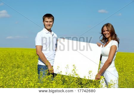 Portrait of happy young couple with blank paper standing in meadow