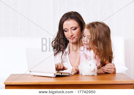 Sweet child looking at the laptop with her mother, white rabbit beside them