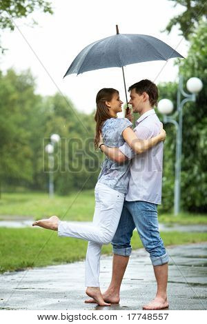 Portrait of woman and man embracing under umbrella during rain