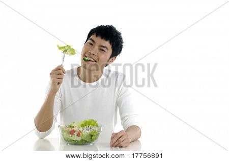 Close up portrait of happy young man eating salad