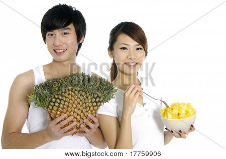 Young man showing pineapple and girl eating fresh fruit