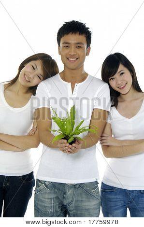 junge Menschen auf eine kleine Pflanze mit zwei Mädchen halten