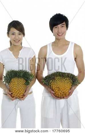 Happy couple showing a healthy fruit