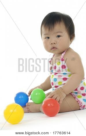Cute girl looking up with colorful ball