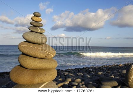 Stack of stones on the beach at sunset time