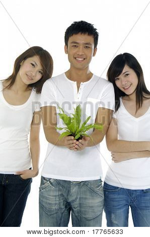 Two beautiful and man holding a growing plant