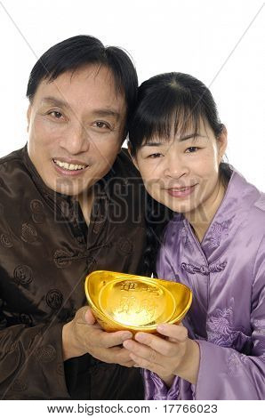 Oriental couple holding big golden nugget.