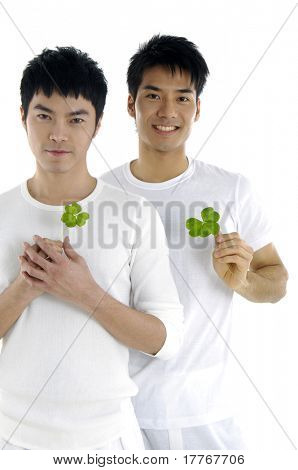 Two young man hands holding leaf
