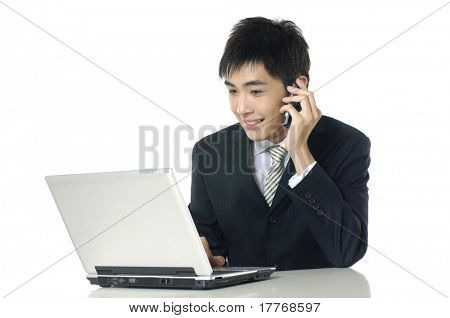 Businessman working on laptop and calling on phone,