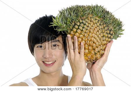 Happy young man showing big pineapple