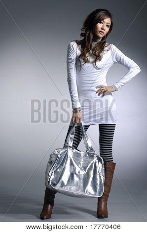 Beautiful fashion model with a handbag posing on light background