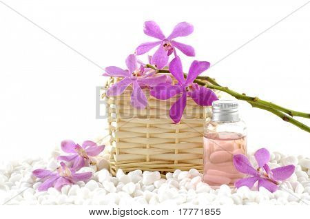 Spa still life with basket of pink orchid and massage oil on zen white pebble