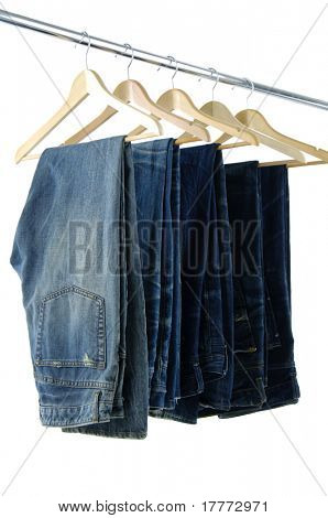 Blue jeans and trousers on wooden hangers