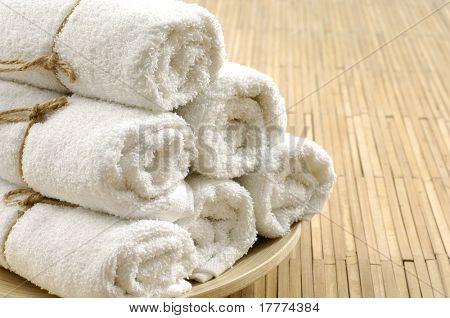 white towels stacked on the bamboo mat