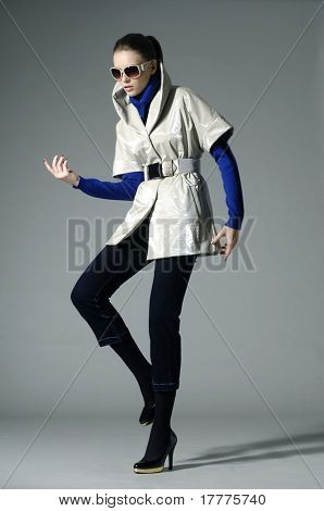 Beautiful fashion model in autumn clothes posing over white background