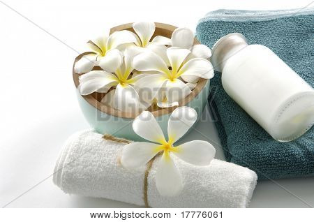 Relaxing spa scene with a white rolled up towel, and white flower