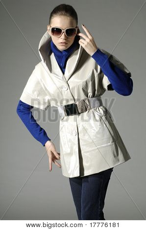 fashion model in autumn/winter clothes posing on light background