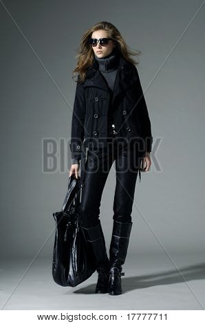 Fashion model with bag. posing in the studio
