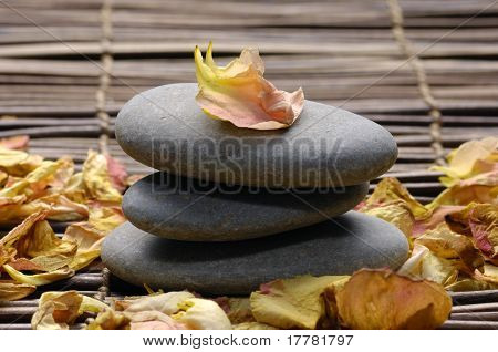 Stack of stone with rose withered petals