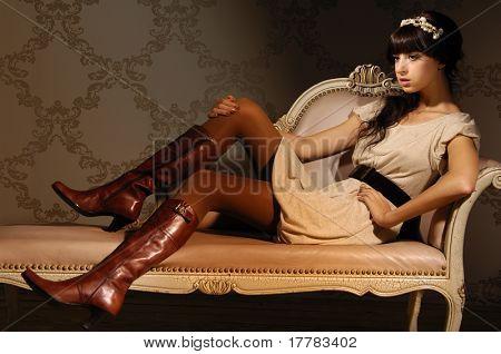 Belo modelo sentado em um sofá de luxo