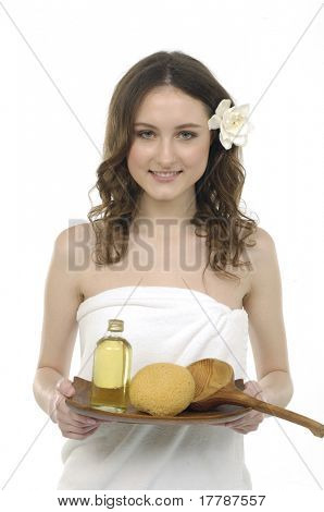 Young woman holding a tray with lotion and washtub, white towels