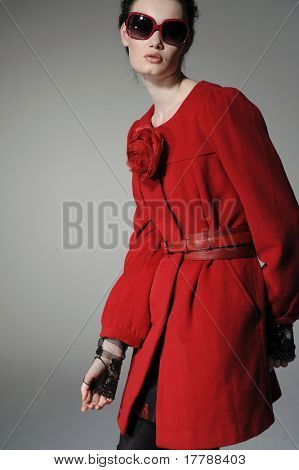 fashion model in red dress posing on gray background