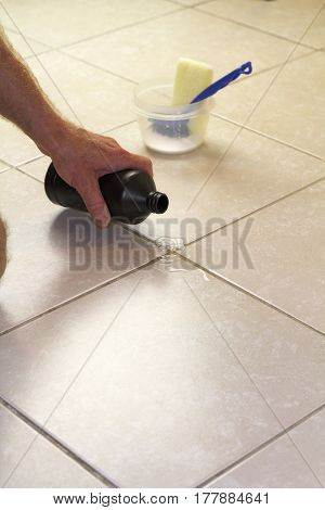 Hand pouring hydrogen peroxide on bathroom floor tile grout. Putting hydrogen peroxide on floor grout with baking soda scrub brush and scrub sponge in back.