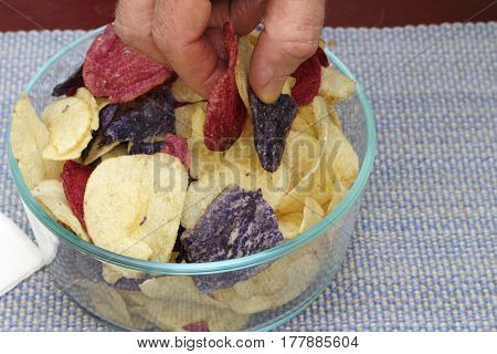 Fingers grasping red white and blue potato chips from a bunch in a bowl. Fingers picking up Red Crimson Purple Majesty and Chipeta or Atlantic potato chips.