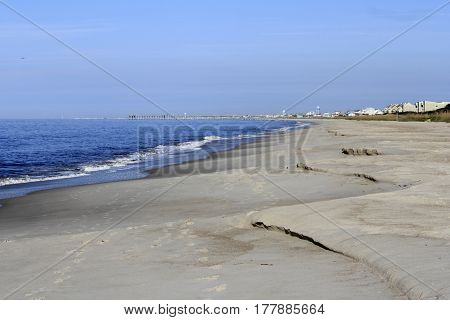 Coast with some mildly steep areas of erosion after a mild storm. Beach cliffing on a shore after a storm on a sunny day.