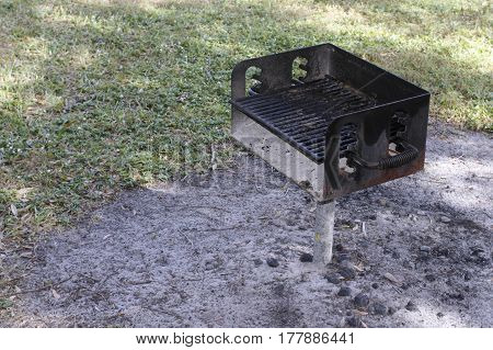 One small barbecue on a pole attached to the ground outside near grass on a sunny day. Barbecue grill on a metal stand in dirt near a lawn during the day.