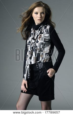 fashion model in fashion dress posing on gray background