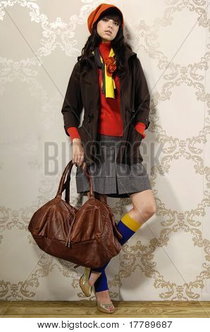 High fashion model with handbag posing in the studio