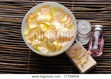 bowel of rose petals and bottle of essential oil with soap on bamboo mat