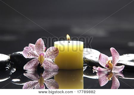 Aromatic candles and orchid flower for spa objects, reflection