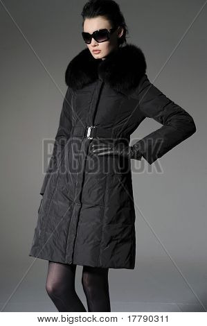 High fashion model in winter fur coat clothes posing- gray background